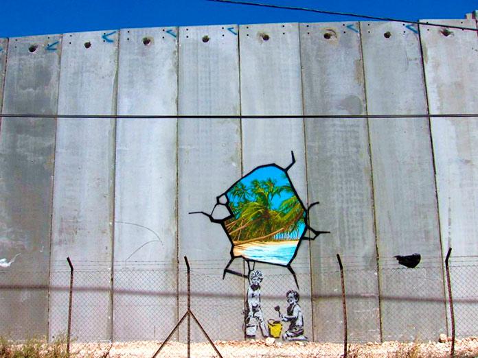 Muro de la vergüenza con un hueco que deja ver una playa paradisiaca y dos ninos delante con cubos y rastrillos