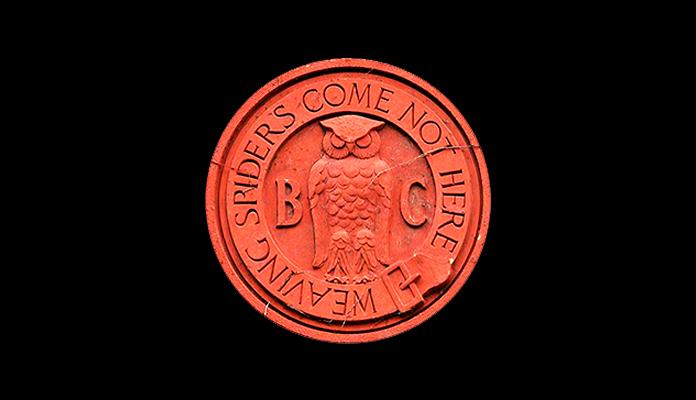 """Símbolo del Bohemian Club con un búho flanqueado por las letras B y C y rodeado por el lema """"Weaving Spiders Come Not Here"""" (""""Las arañas que tejen no vienen aquí"""")"""