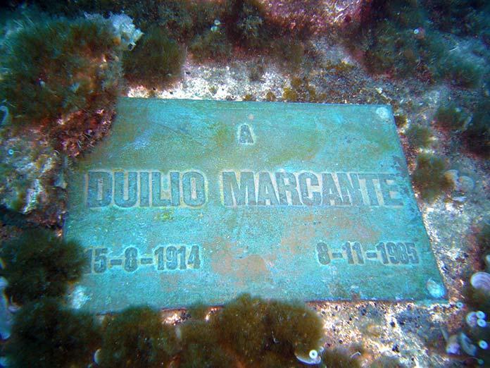 Placa conmemorativa a Duilio Marcante en la base del Cristo del abismo.