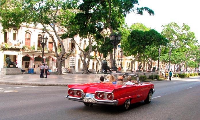 Coche descapotable recorre el Paseo del Prado con turistas a bordo