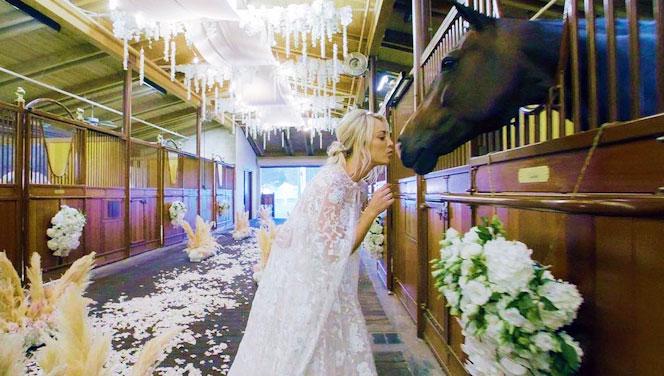 Kaley Cuoco vestida de novia besando a uno de los caballos