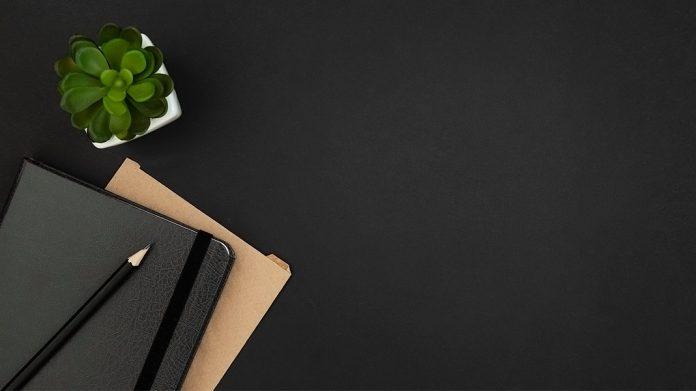 agenda junto a una planta sobre una mesa negra