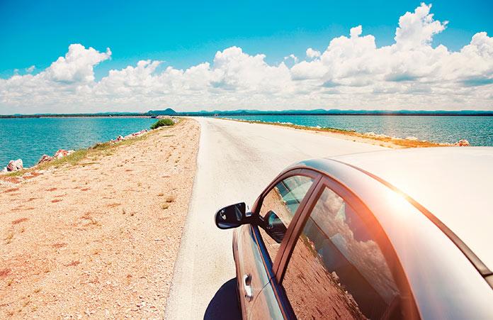 Coche circulando por una carretera al borde del mar