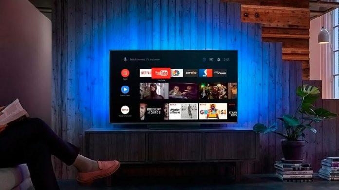 persona sentada viendo en el televisor la pantalla de menú de Android TV