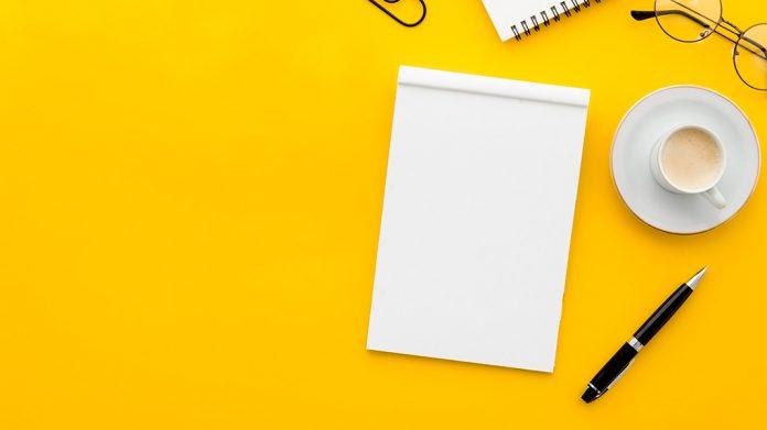 cuaderno de anotaciones, bolígrafo y café sobre mesa amarilla