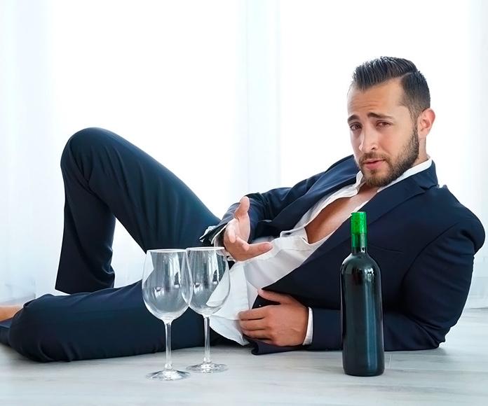 Antonio Suleiman recostado en el suelo frente a una botella de vino y dos copas