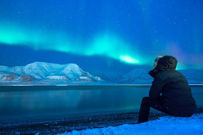 Hombre contemplando la Aurora Boreal