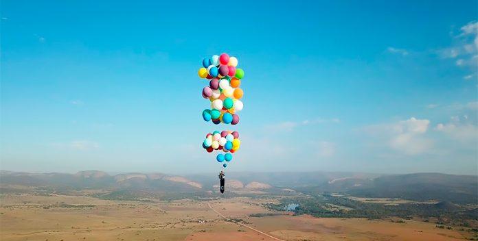 Un aventurero sobrevuela Sudáfrica suspendido en una silla con globos.