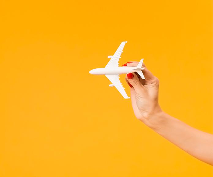 mano de mujer jugando con una avión de juguete
