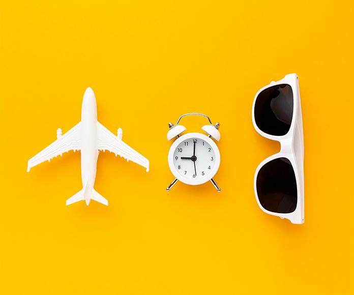 un avión de juguete junto a un despertador y unas gafas