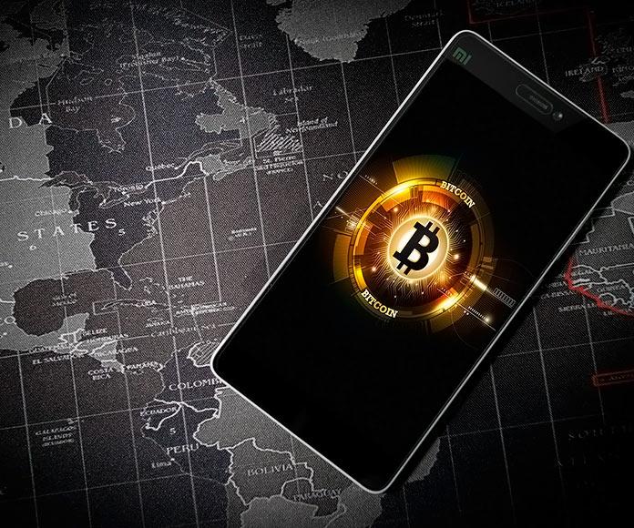 Símbolo del bitcoin en un smartphone con un mapa del mundo de fondo