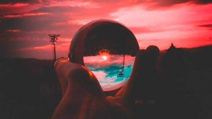 mano sujetando una bola de cristal al amanecer