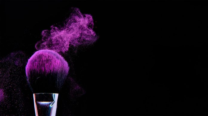 brocha de maquillaje esparciendo maquillaje violeta