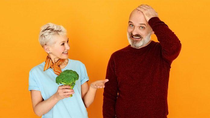 mujer mayor ofreciendo un brócoli a su marido