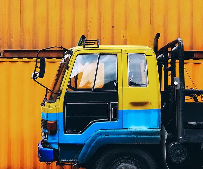 camión aparcado frente a un contenedor amarillo