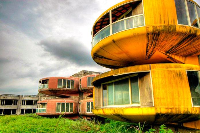 Casa OVNI amarilla frente a otra de color rosa