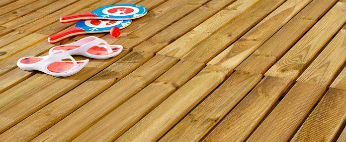 Un par de cholas, raquetas y una pelota en un suelo de madera