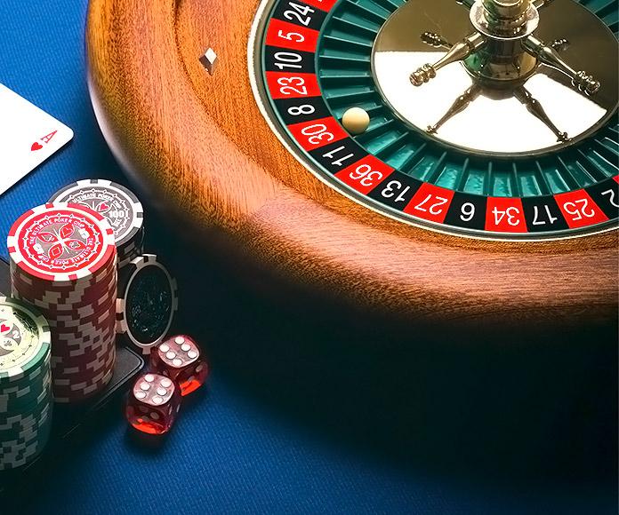 ruleta y fichas de casino junto a un ordenador portátil