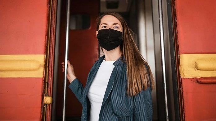chica con mascarilla bajando de un autobús