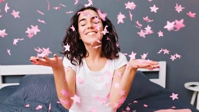 chica feliz tirando confeti en forma de estrella sobre su cama