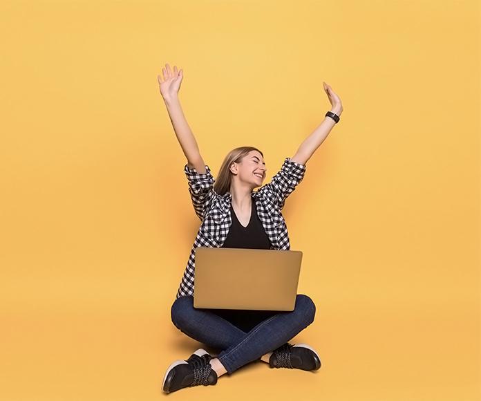 chica feliz con un ordenador portátil sobre sus piernas