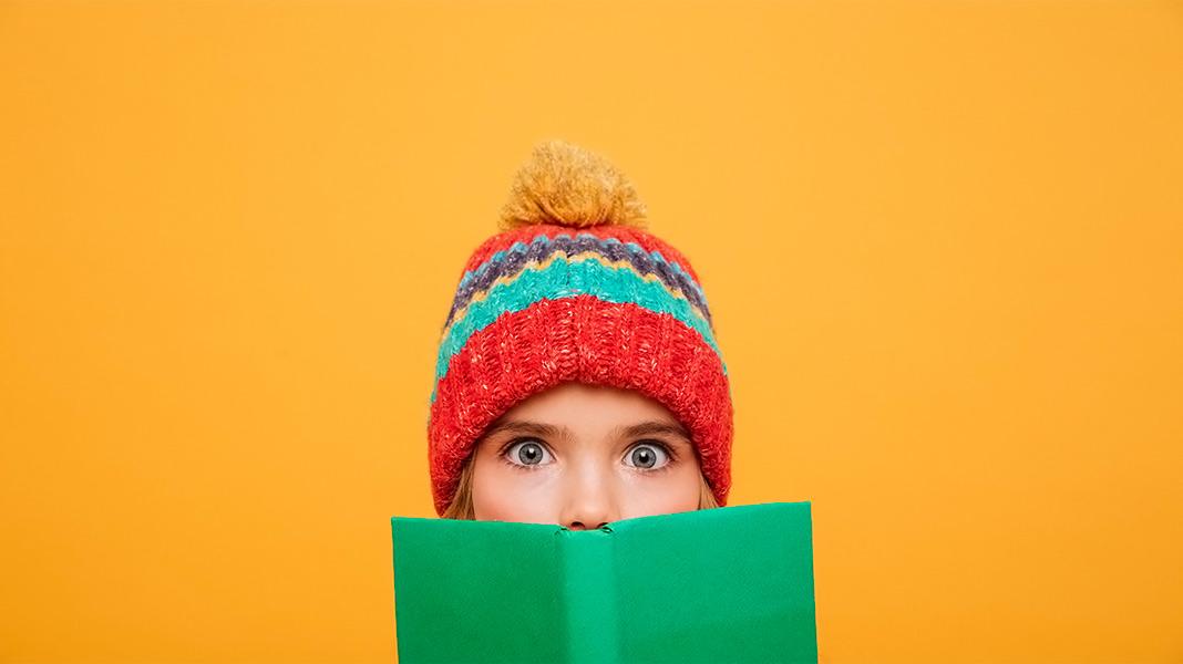 chica con gorro de invierno detrás de un libro