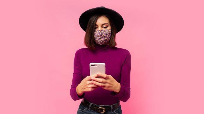 chica con mascarilla usando el teléfono móvil