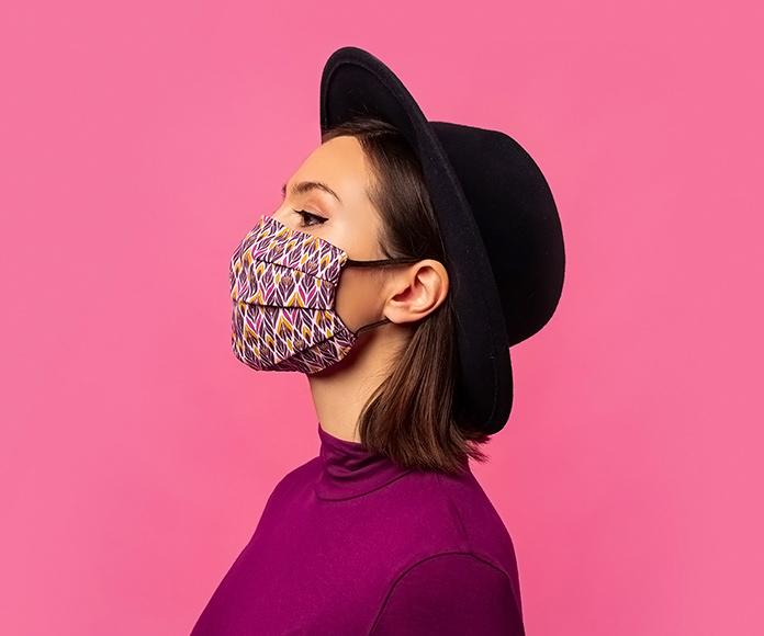 chica de perfil con sombrero negro y mascarilla de diseño