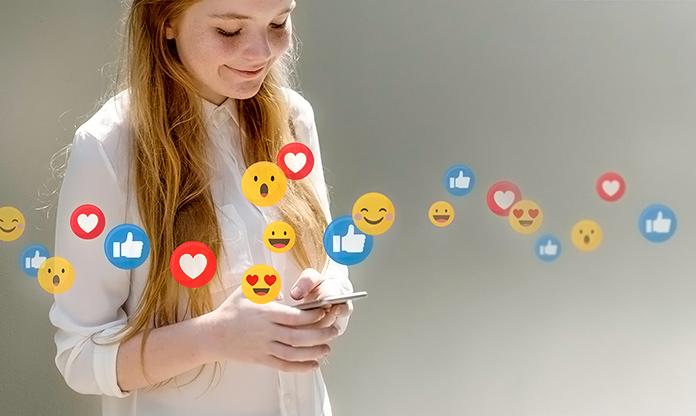 Chica utilizando el móvil rodeada de iconos de redes sociales
