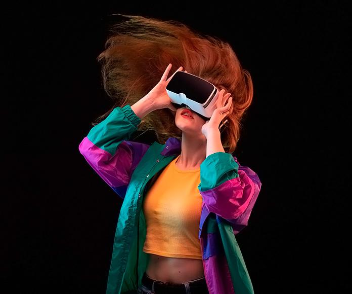 chica con el pelo en movimiento usando unas gafas de realidad virtual