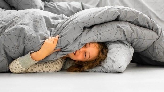 chica sonriente en la cama bajo la colcha