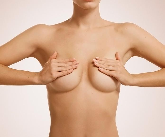 chica desnuda tapándose los pechos con las manos