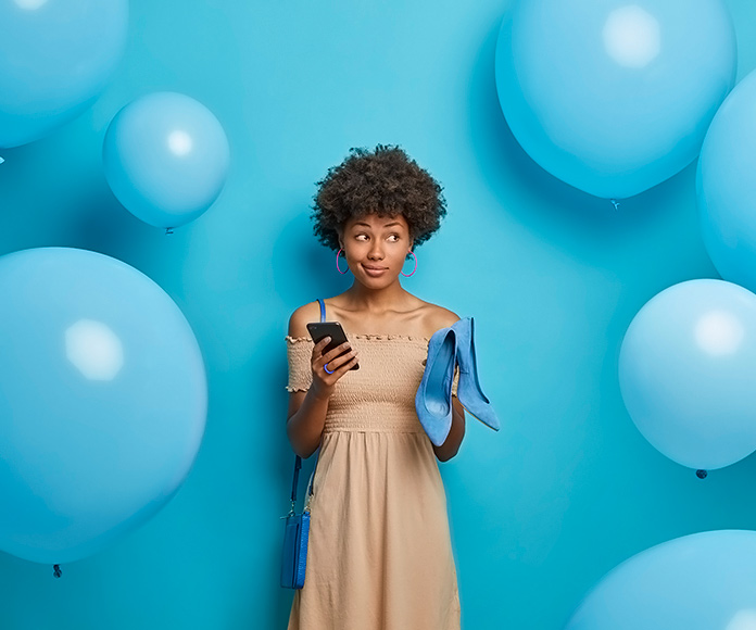 chica rodeada de globos sujetando unos zapatos