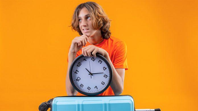 chico esperando con una maleta de viaje y un reloj de pared