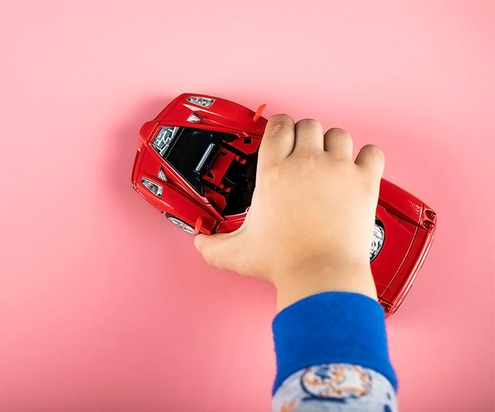 mano de niño jugando con un coche deportivo en miniatura