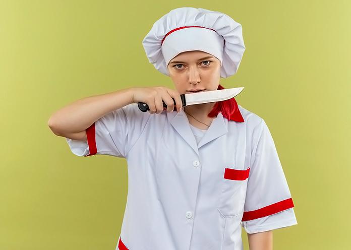cocinera enseñando un cuchillo con cara de asesina