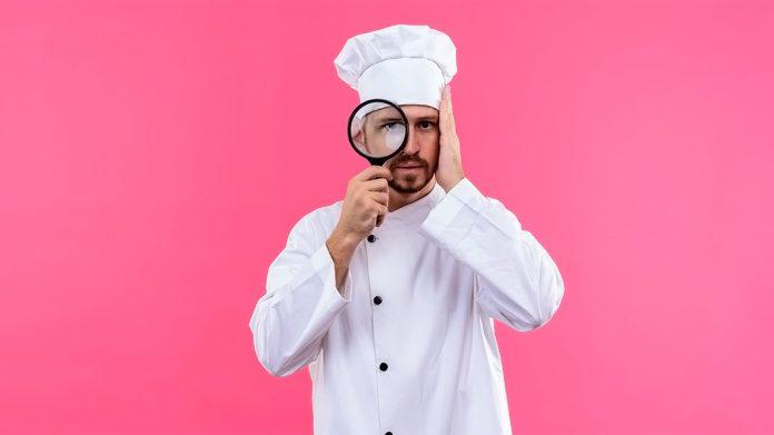 cocinero mirando a través de una lupa con cara de asombro
