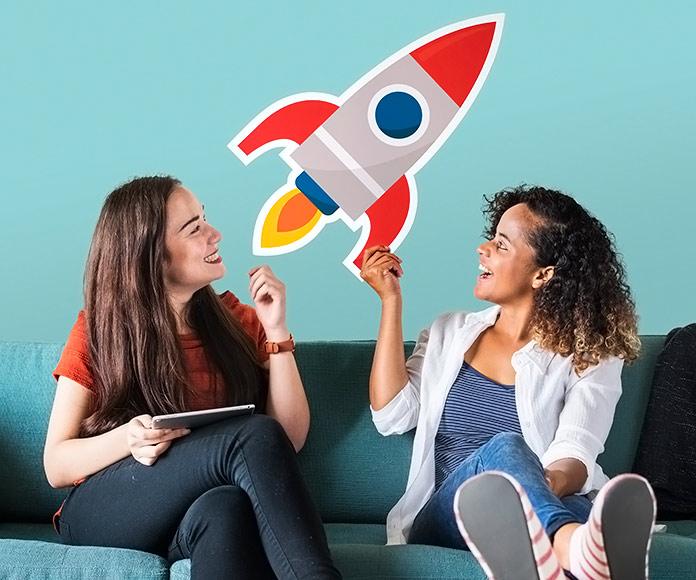 dos chicas sonrientes sujetando un dibujo de un cohete