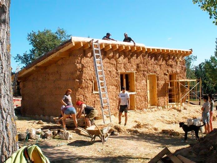 Grupo de personas construyendo una casa con fardos de paja