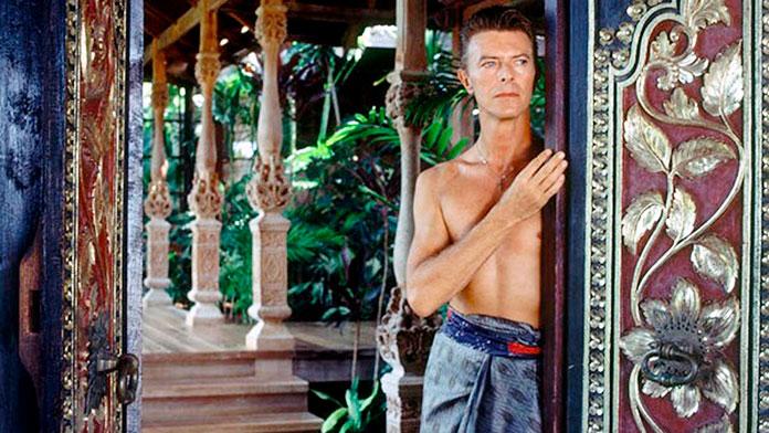David Bowie posando al lado de una puerta balinesa de su villa ubicada en la exclusiva Isla de Mustique