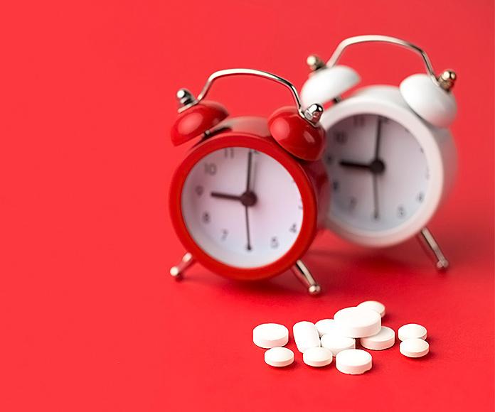relojes despertadores junto a complementos vitamínicos
