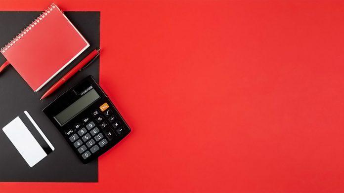 calculadora, tarjeta de crédito y libreta sobre escritorio rojo