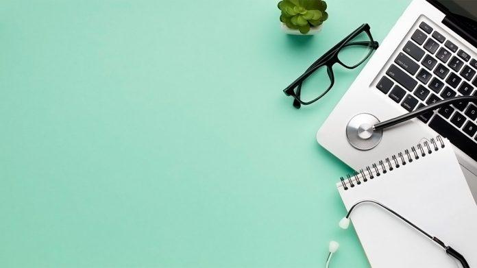 un estetoscopio, unas gafas y un ordenador portátil sobre una mesa verde