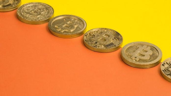 fila de bitcoins sobre fondo amarillo y naranja
