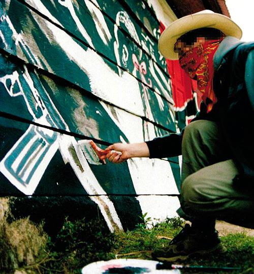 Foto de la cara de Banksy mientras termina una de sus obras en México.