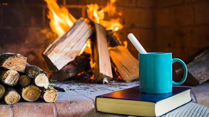 libro y taza de desayuno junto a chimenea encendida