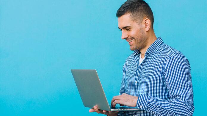 hombre sonriente sujetando un ordenador portátil
