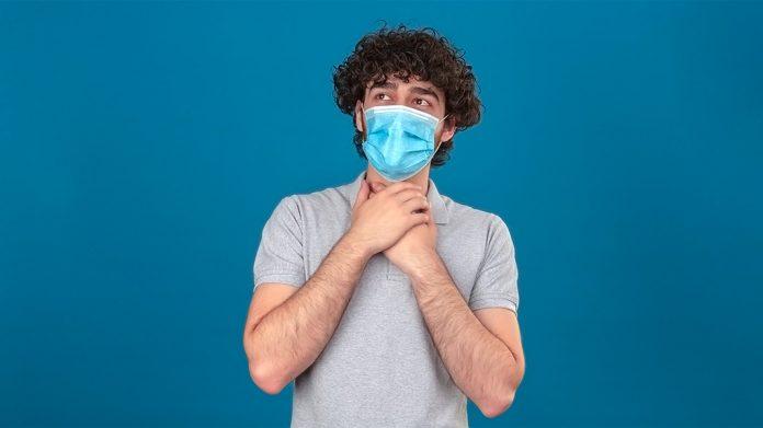 hombre con mascarilla tocándose la garganta con las dos manos