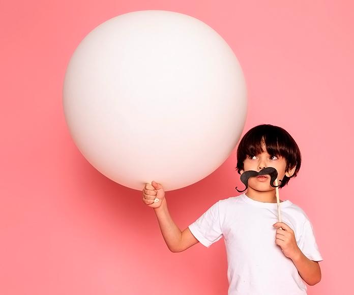 niño con un bigote de papel sujetando un globo blanco
