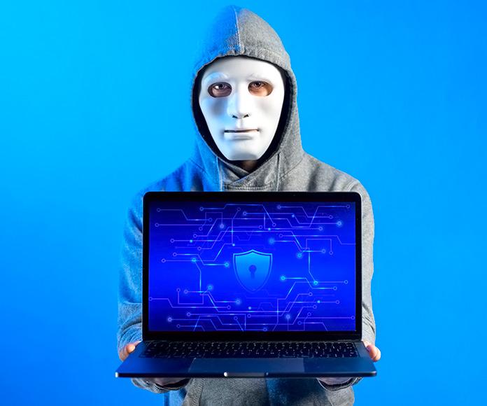 hacker enseñando un ordenador con un escudo en la pantalla